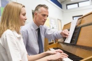 Teacher with schoolgirl playing piano in music class